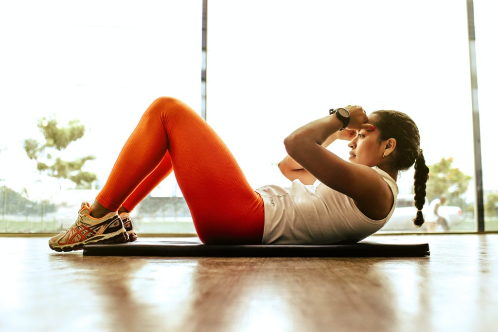 a person doing crunches, wearing a white shirt and orange pants